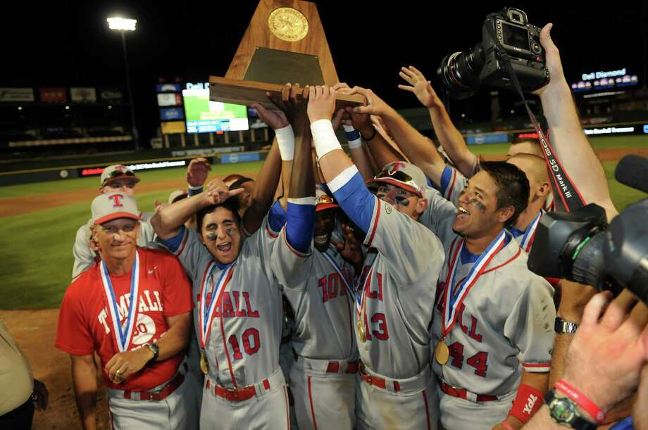Tomball head coach Doug Rush, from left, is all smiles as Kyle Workman, Ishmael Edwards, Nick Banks, and Stephan Bonnain hoist the Cougar's 2013 Class 4A UIL State Baseball Championship trophy after their 6-1 win over Corpus Christi Moody at Dell Diamond in Round Rock on Friday. Photo: Jerry Baker, For The Chronicle