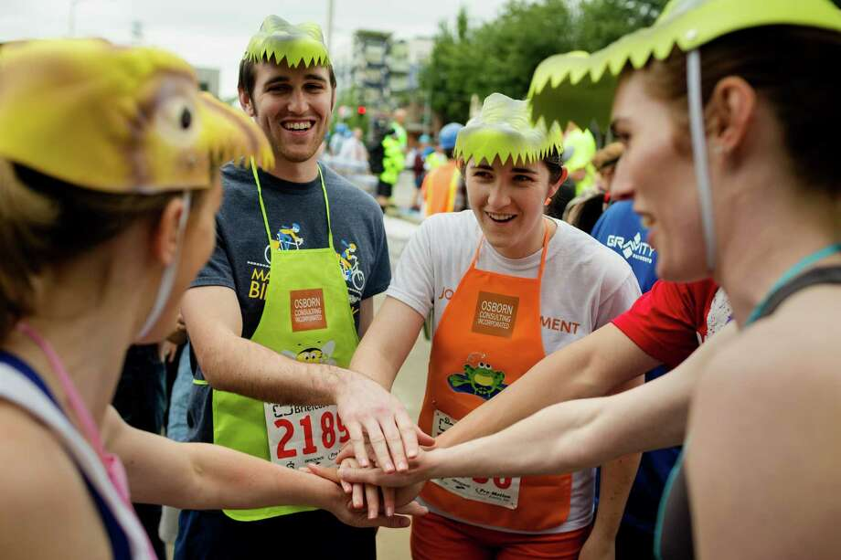 A team of dinosaur-headed participants get pumped before the annual Fremont 5K and Briefcase Relay Friday, June 7, 2013, in Fremont. For the relay, teams of five are dressed in business attire from the waist up, and each team member runs a kilometer carrying the team's briefcase, filled with five cans of food to donate at the end of the spectacle. Photo: JORDAN STEAD, SEATTLEPI.COM / SEATTLEPI.COM