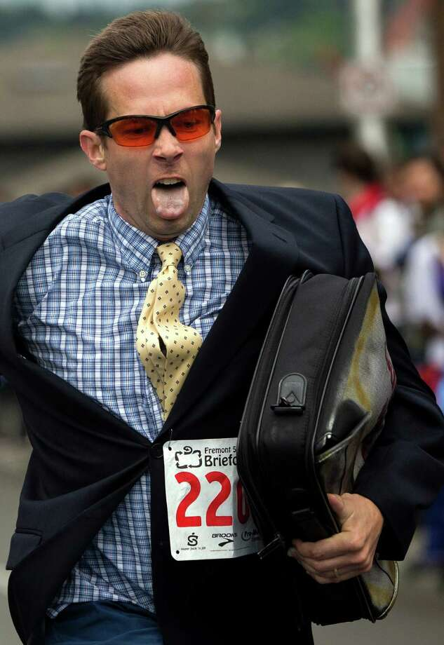 Decked out in colorful, humorous costumes, runners warm up and enjoy in the annual Fremont 5K and Briefcase Relay Friday, June 7, 2013, in Fremont. For the relay, teams of five are dressed in business attire from the waist up, and each team member runs a kilometer carrying the team's briefcase, filled with five cans of food to donate at the end of the spectacle. Photo: JORDAN STEAD, SEATTLEPI.COM / SEATTLEPI.COM