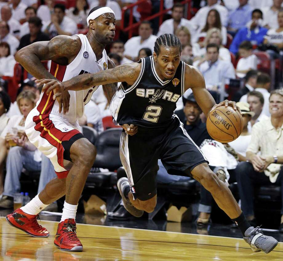 The Spurs' Kawhi Leonard drives around Miami's LeBron James during Game 1. James finished with a triple-double (18 points, 18 rebounds, 10 assists), but the second-year forward helped hold the reigning MVP eight points below his postseason average. Photo: Edward A. Ornelas / San Antonio Express-News