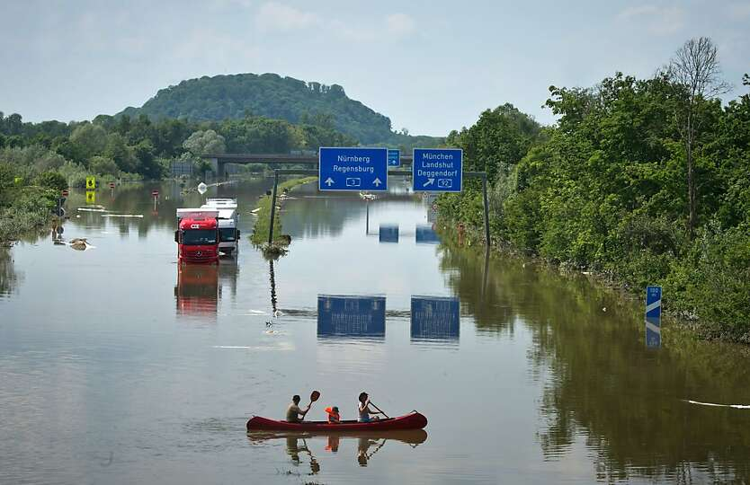 A family canoe past vehicles which lay stranded on the A3 autobahn after the swollen Danube river bu