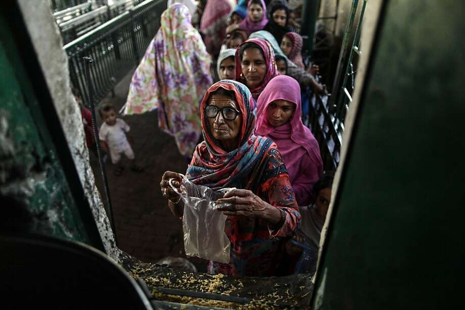 Hoping for a ration of rice, an elderly Pakistani woman waits with bag ready at a shrine in Islamabad. Worshippers who visit shrines and offer prayers often bring food for the poor. Photo: Muhammed Muheisen, Associated Press