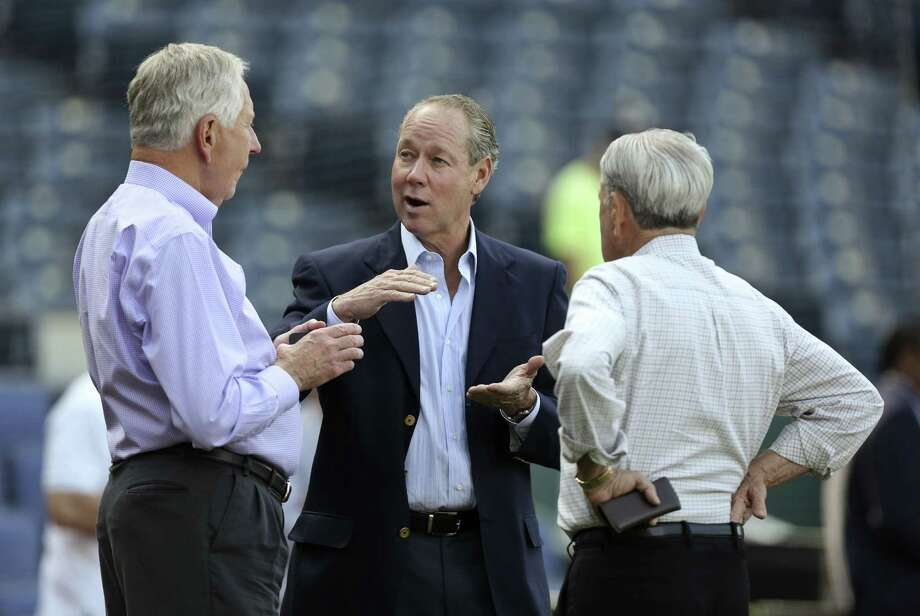 In a meeting of men with rebuilding experience, Astros owner Jim Crane talks with former owner Drayton McLane and Royals owner David Glass, right. Photo: Ed Zurga, Stringer / 2013 Getty Images