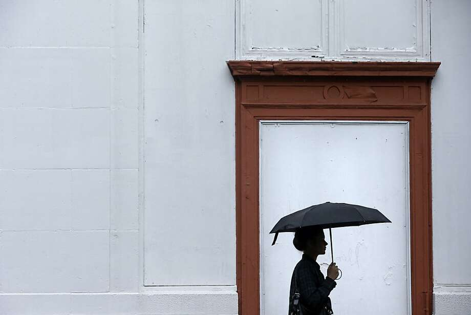A woman walks shielded from a rainstorm with an umbrella, Friday, June 7, 2013, in Philadelphia. The National Weather Service has issued a flash flood watch for much of southeastern Pennsylvania as remnants of Tropical Storm Andrea move through the region. (AP Photo/Matt Rourke) Photo: Matt Rourke, Associated Press