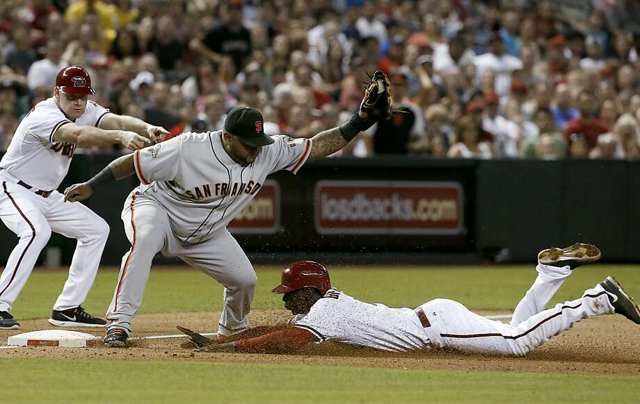Arizona Diamondbacks' Didi Gregorius, right, slides into third base ahead of the tag by San Francisco Giants' Pablo Sandoval, advancing to third base on a fly out by a teammate, during the fifth inning in a baseball game Friday, June 7, 2013, in Phoenix. (AP Photo/Ross D. Franklin) Photo: Ross D. Franklin, Associated Press