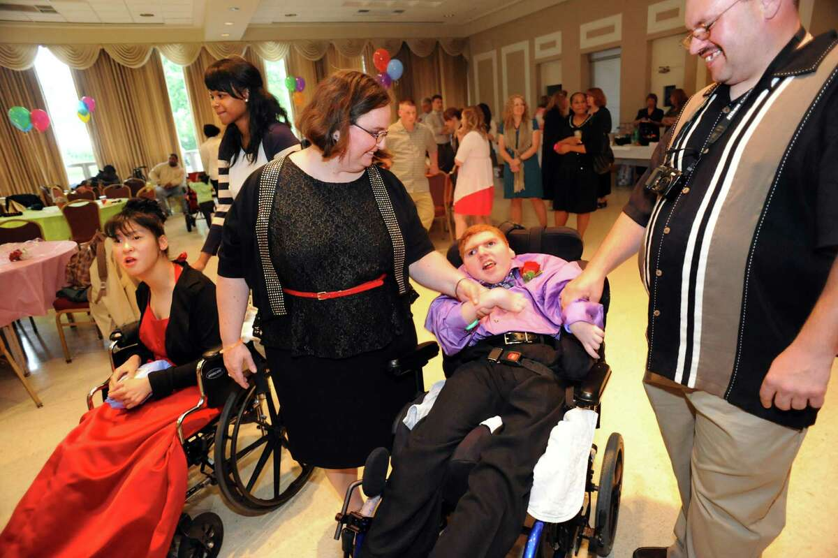 Mary Kay Kelly of Queensbury, center, and friend Matt Sumner, right, dance with her son Bryan Vaillancourt, 15, during the annual Langan School Prom on Friday, June 7, 2013, at St. Sophia Greek Orthodox Church in Albany, N.Y. Students dressed their best, danced to a D.J.'s music and posed for official photos. The Langan School, which is for students who have disabilities or severe medical conditions, believes in offering students the same experiences as any other school. (Cindy Schultz / Times Union)