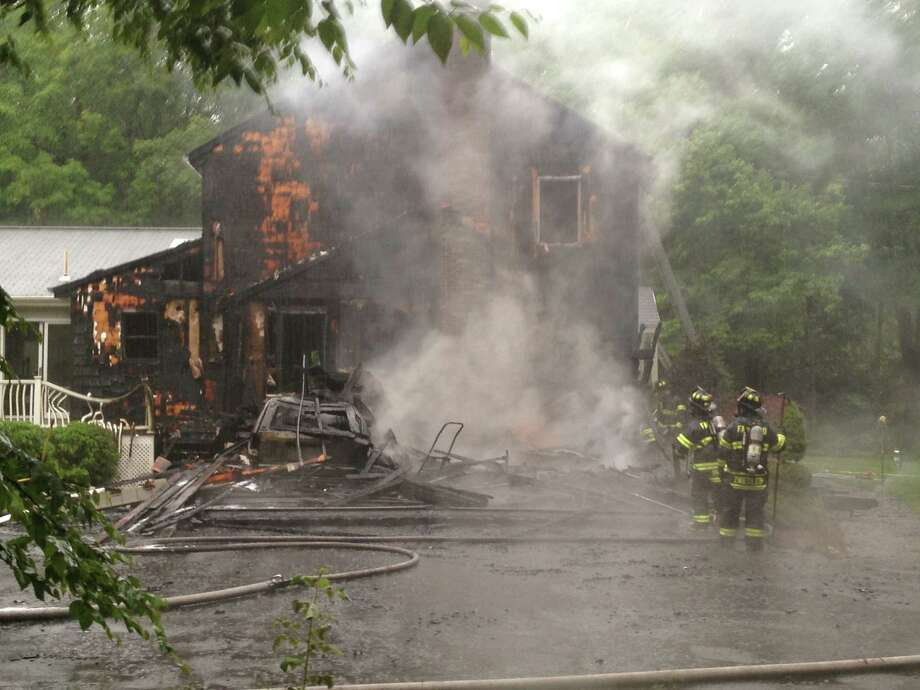 A garage attached to a home in Greenfield Hills burned to the ground Friday, although firefighters managed to keep the fire from taking the house as well. Photo: Denis O'Malley / Connecticut Post