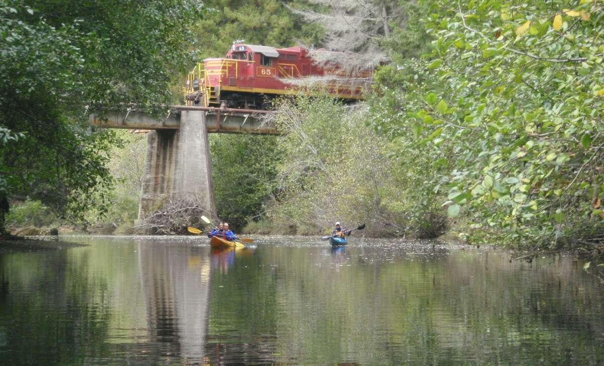 The Skunk Train's diesel locomotive emerges from Tunnel #1 (now closed) and crosses the Noyo River as kayakers paddle back towards Noyo Harbor. The Skunk train offers a ''Tracks to Kayaks'' trip in the late spring, summer and early fall.