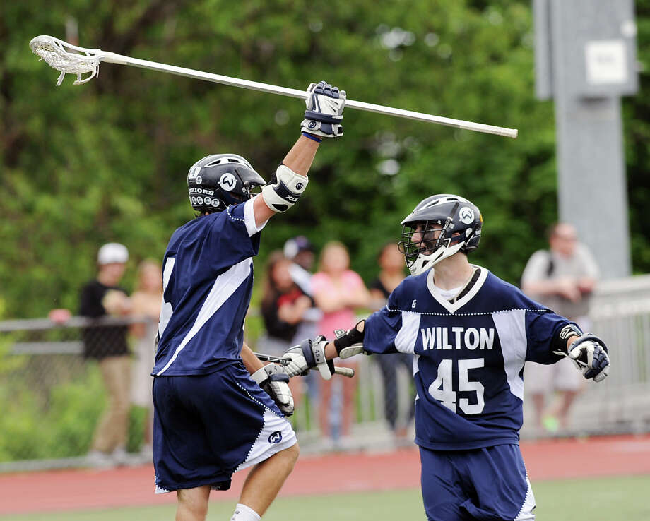 At left, Henry Lee (# 4) of Wilton, raises his stick overhead after scoring during the Division M boys high school lacrosse championship between Joel Barlow High School and Wilton High School at Brien McMahon High School in Norwalk, Saturday, June 8, 2013. At right is Lee's teammate Brendan Devane (# 45). Wilton took the title with a 9-4 victory. Photo: Bob Luckey / Greenwich Time