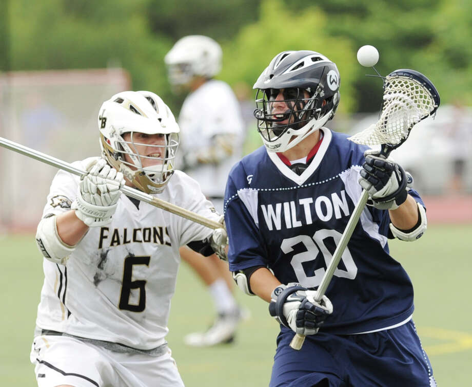 At left, Mike Kearney (# 6) of Joel Barlow defends against Wilton's Luke Reyes Guerra Dunn (# 20) during the Division M boys high school lacrosse championship between Joel Barlow High School and Wilton High School at Brien McMahon High School in Norwalk, Saturday, June 8, 2013. Wilton took the title with a 9-4 victory. Photo: Bob Luckey / Greenwich Time