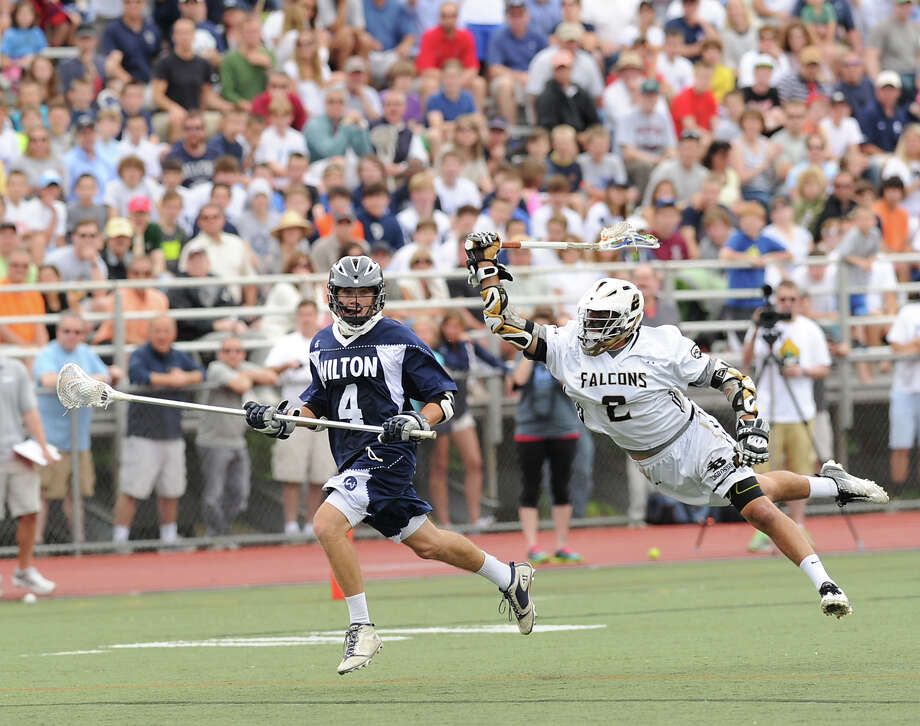 At left, Henry Lee (# 4) of Wilton breaks down-field as Luke Maroun (# 2) of Joel Barlow dives for the stick check during the Division M boys high school lacrosse championship between Joel Barlow High School and Wilton High School at Brien McMahon High School in Norwalk, Saturday, June 8, 2013. Wilton took the title with a 9-4 victory. Photo: Bob Luckey / Greenwich Time