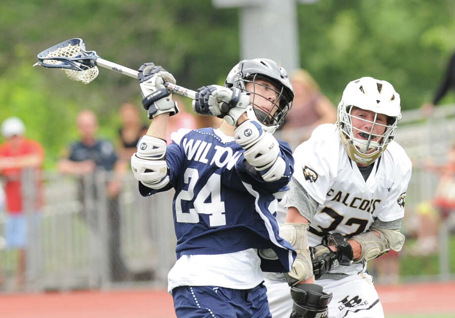 At left, Wilton's Mike Burns (# 24) shoots as Finn Cohane (# 32) of Joel Barlow defends during the Division M boys high school lacrosse championship between Joel Barlow High School and Wilton High School at Brien McMahon High School in Norwalk, Saturday, June 8, 2013. Wilton took the title with a 9-4 victory. Photo: Bob Luckey / Greenwich Time