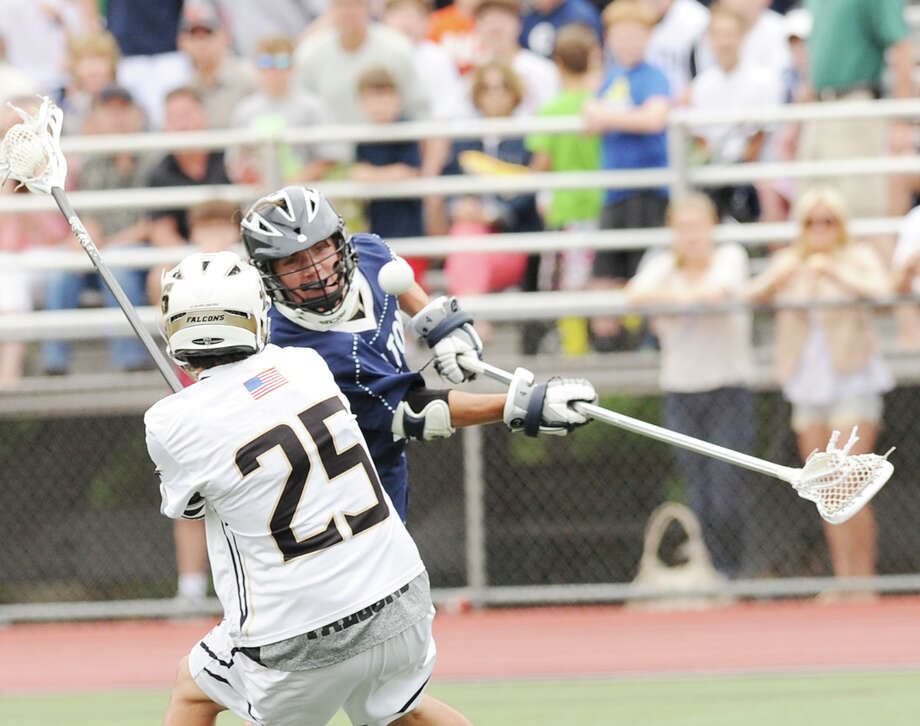 At right, Henry Lee of Wilton scores while being defended by Zack Healy (# 25) of Joel Barlow during the Division M boys high school lacrosse championship between Joel Barlow High School and Wilton High School at Brien McMahon High School in Norwalk, Saturday, June 8, 2013. Wilton took the title with a 9-4 victory. Photo: Bob Luckey / Greenwich Time