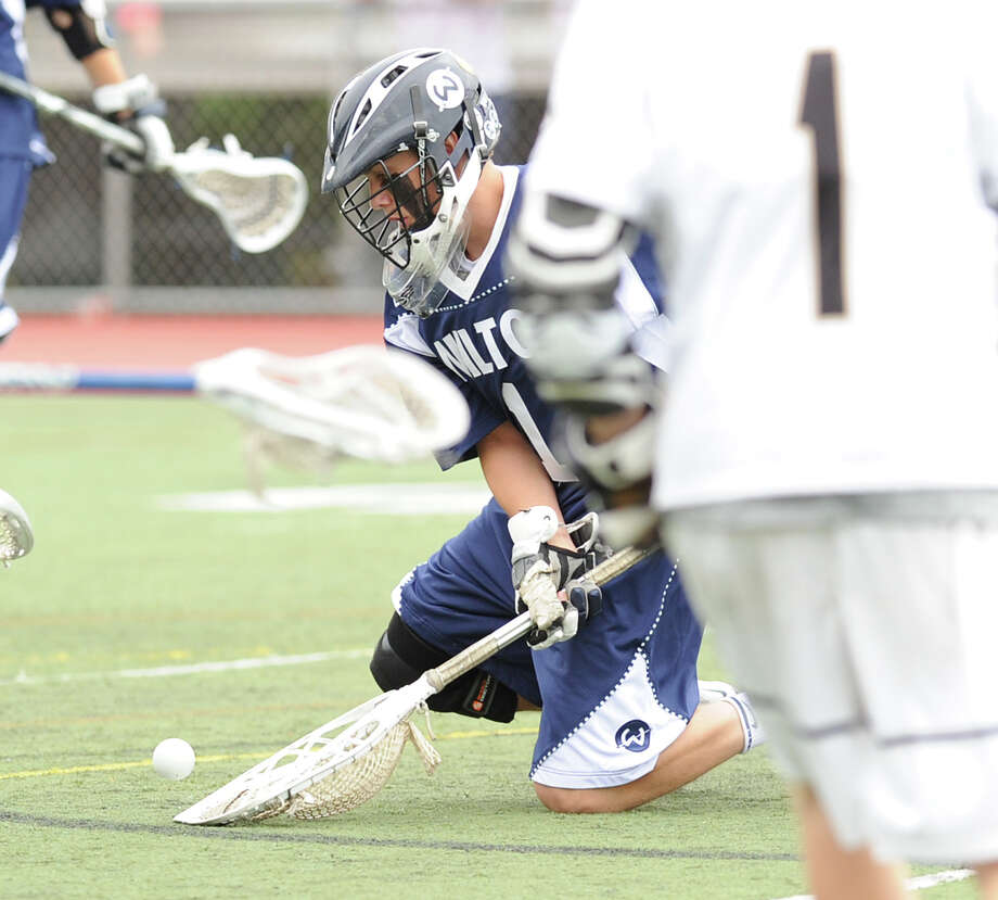 At left, Wilton goalie Connor Johnson scoops up his blocked shot during the Division M boys high school lacrosse championship between Joel Barlow High School and Wilton High School at Brien McMahon High School in Norwalk, Saturday, June 8, 2013. Wilton took the title with a 9-4 victory. Photo: Bob Luckey / Greenwich Time