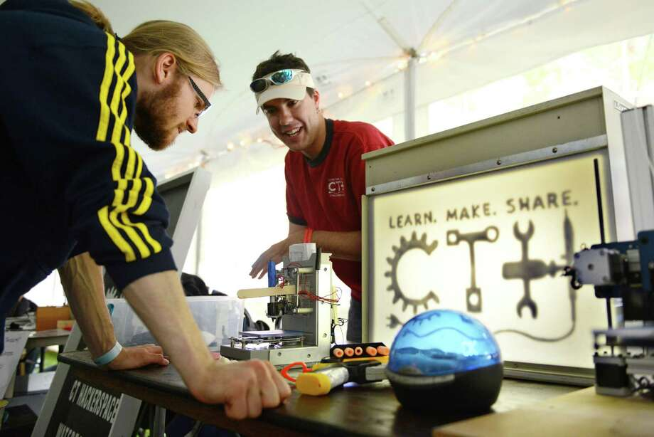Nikki McCavee, left, of Detroit, and Rich Bremer, of Connecticut Hackerspace, chat at the CT Hackerspace booth at the Danbury Mini Maker Faire at CityCenter Danbury Green on June 8, 2013.  The festival featured dozens of exhibits from craftsmen, engineers, inventors and artists. Photo: Tyler Sizemore / The News-Times