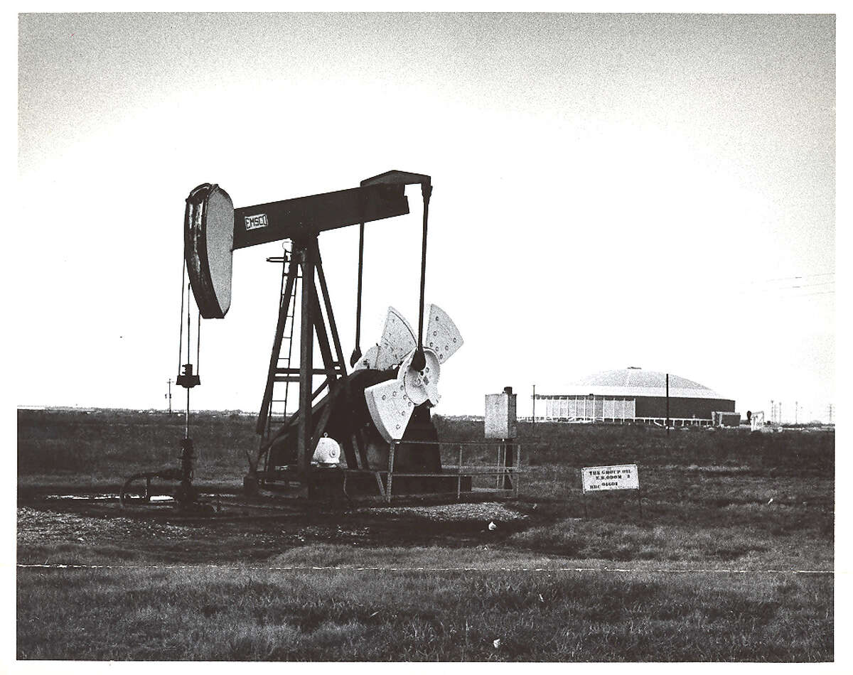 A pumpjack works in foreground of the Astrodome in 1965. For many, the two structures are iconic images of Houston.