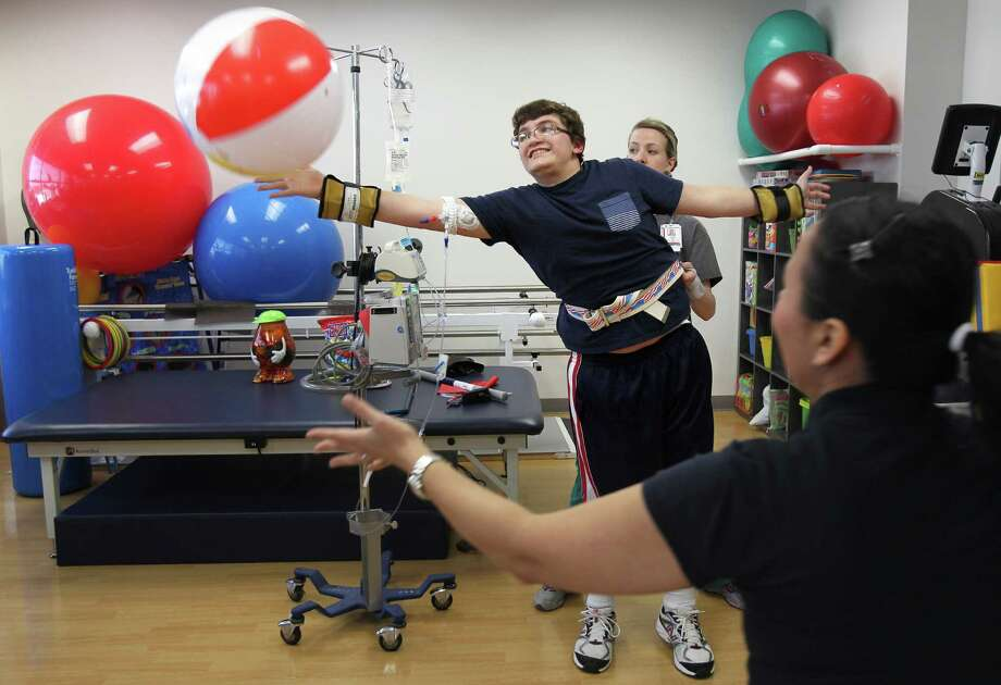 Patient Isaiah Goertz reaches out for a beach ball while    Occupational Therapist Layne Childs stands by as they try to improve Goertz balance during his therapy sessions at Texas Children's Hospital where he is recovering from a flesh eating bacteria on Tuesday, May 21, 2013, in Houston. Photo: Mayra Beltran, Houston Chronicle / © 2013 Houston Chronicle
