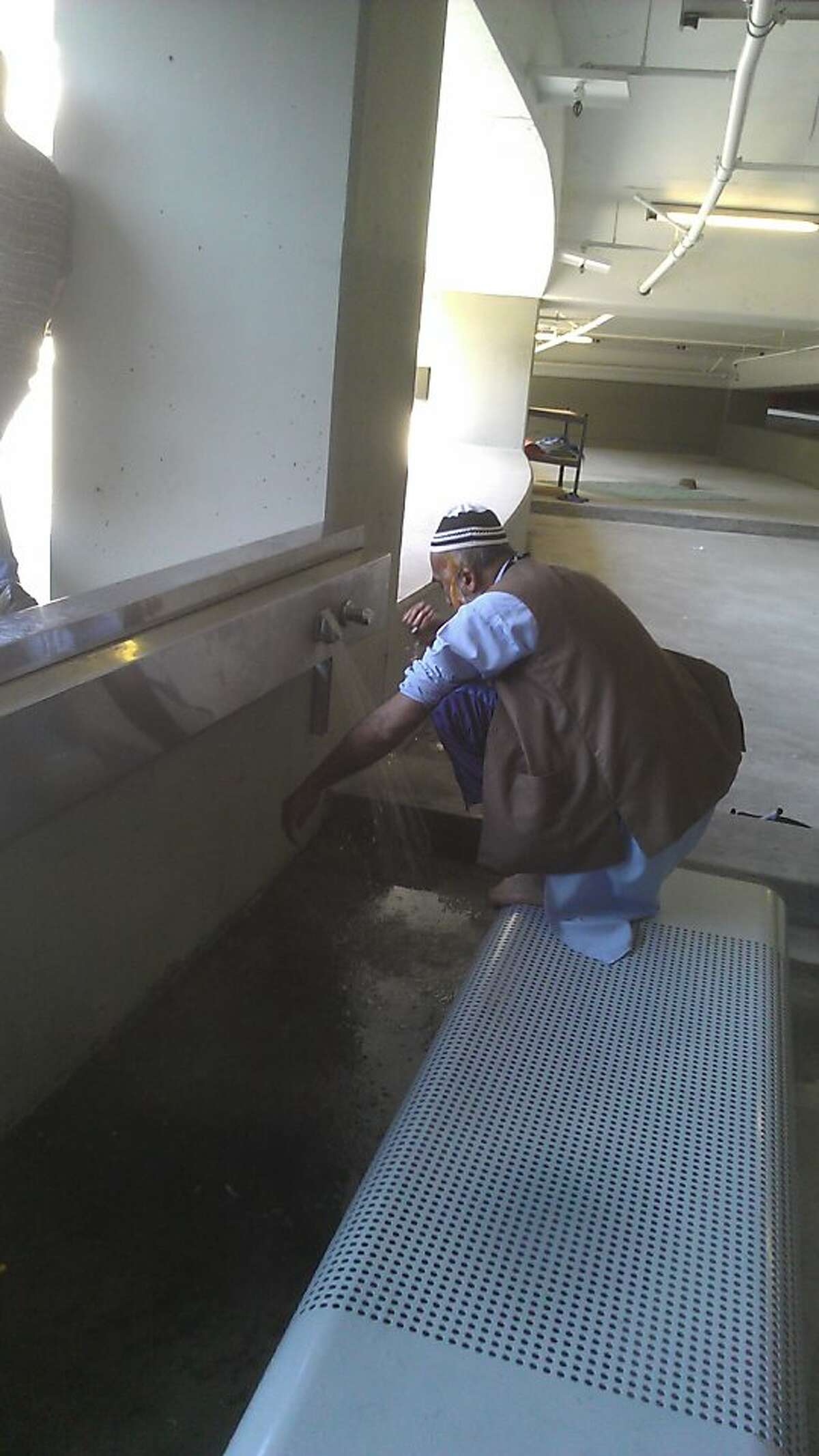Royal cab driver Hasan Khan, 52, washes his hands and feet inside the parking garage at San Francisco International Airport before his his daily prayers. Khan's petition drive prompted the airport to give the Muslim drivers their own cleansing station.
