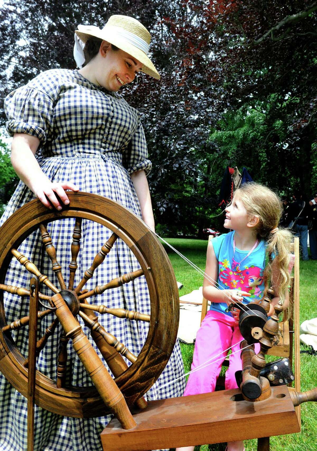 Emily Wompisik Unnokon tells Isabella Macri, 7, about a 1770 flax wheel during a Soldiers Fair, with re-enactors recreating camp life and expierences shared by Union soldiers 150 years ago, at Ballard park in Ridgefield, Conn. Saturday, June 8, 2012.
