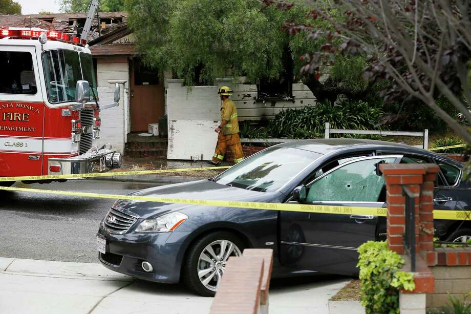 A firefighter walks past a car with bullet holes across a home that caught fire in Santa Monica, Calif. Friday, June 7, 2013. Two people were found dead Friday in a burned home near the school, where someone sprayed a street corner with gunfire, wounding at least three people, authorities said. Photo: Damian Dovarganes