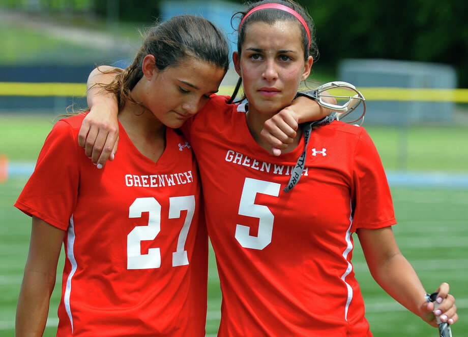 Greenwich's Carolyn Paletta, left, and teammate Emma Christie walk off the field after the team was defeated by Darien, during Class L lacrosse finals action in Stratford, Conn. on Saturday June 8, 2013. Photo: Christian Abraham / Connecticut Post