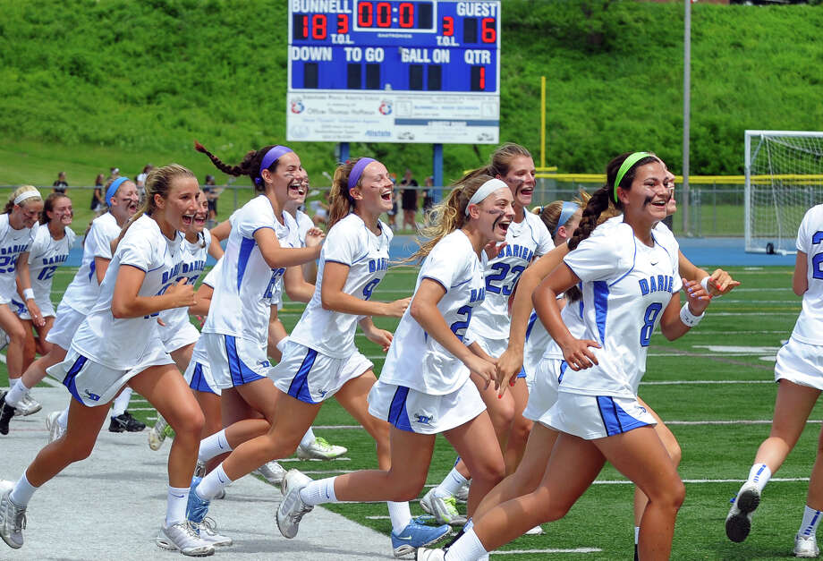Darien team members rush onto the field to celebrate after beating Greenwich, during Class L lacrosse finals action in Stratford, Conn. on Saturday June 8, 2013. Photo: Christian Abraham / Connecticut Post