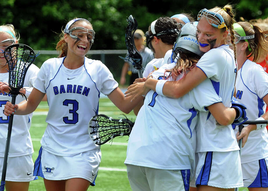 Darien team members hug goalie Caylee Waters and celebrate after beating Greenwich, during Class L lacrosse finals action in Stratford, Conn. on Saturday June 8, 2013. Photo: Christian Abraham / Connecticut Post