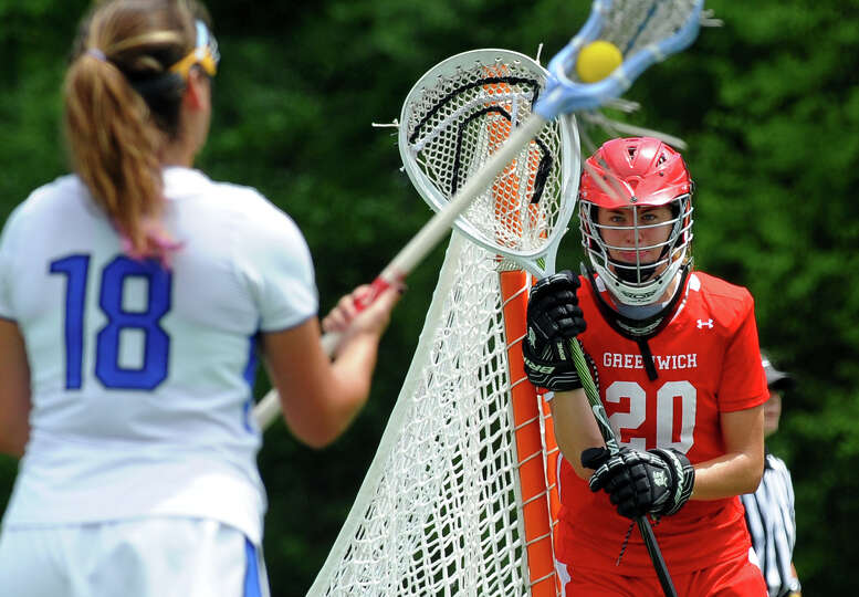 Greenwich goalie Kylie Ginsberg stands ready as Darien's Jena Fritts circles, during Class L lacross
