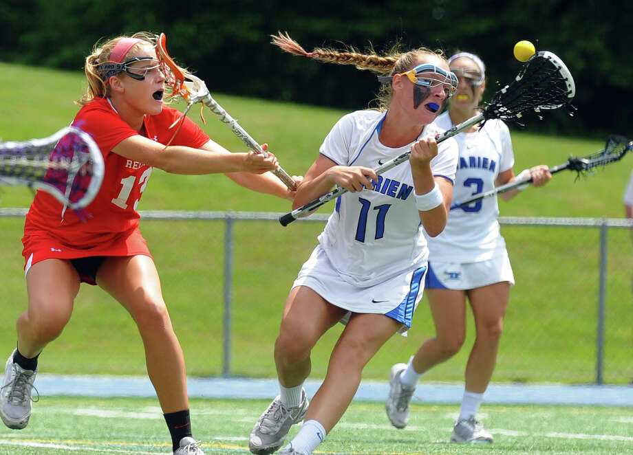 Darien's Kristen Gilbert loses control of the ball after a bump by Greenwich's Jenny Goggin, left, during Class L lacrosse finals action in Stratford, Conn. on Saturday June 8, 2013. Photo: Christian Abraham / Connecticut Post