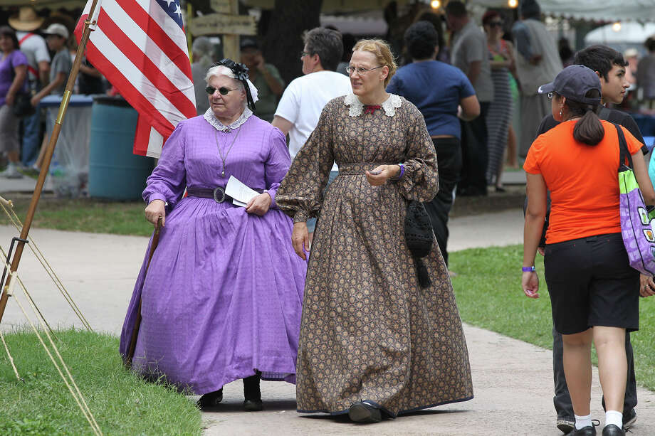 Women dressed in pioneer clothing walk near where actors dressed in 1866 2nd U.S. Artillery uniforms fire a Civil War era replica cannon on the grounds of the Institute of Texan Cultures on June 8, 2013. Photo: TOM REEL