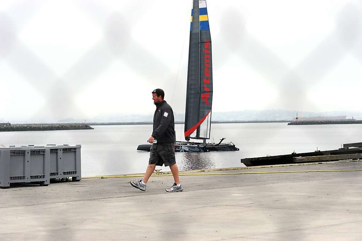 A staff member is seen walking in front an Artemis racing boat on the docks at the Artemis Racing team's facilities in Alameda, CA Friday May 10th, 2013.