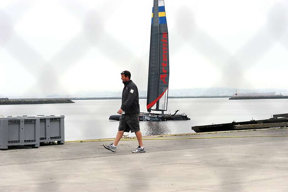 A staff member is seen walking in front  an Artemis racing boat on the docks at the Artemis Racing team's facilities in Alameda, CA Friday May 10th, 2013. Photo: Michael Short, Special To The Chronicle