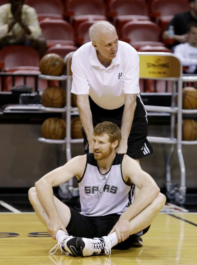 San Antonio Spurs coach Gregg Popovich helps forward Matt Bonner  stretch during basketball practice, Saturday, June 8, 2013, in Miami. The Miami Heat and the Spurs play Game 2 of the NBA Finals on Sunday. (Wilfredo Lee / Associated Press)