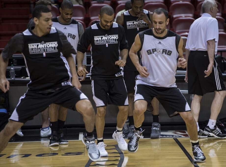 Tony Parker (C) and Manu Ginobili (R) of the San Antonio Spurs warm up with teammates during a practice session for Game 2 of the NBA Finals at the American Airlines Arena on June 8, 2013 in Miami. The San Antonio Spurs won Game 1 against the Miami Heat 92-88.   AFP PHOTO/Brendan SMIALOWSKIBRENDAN SMIALOWSKI/AFP/Getty Images
