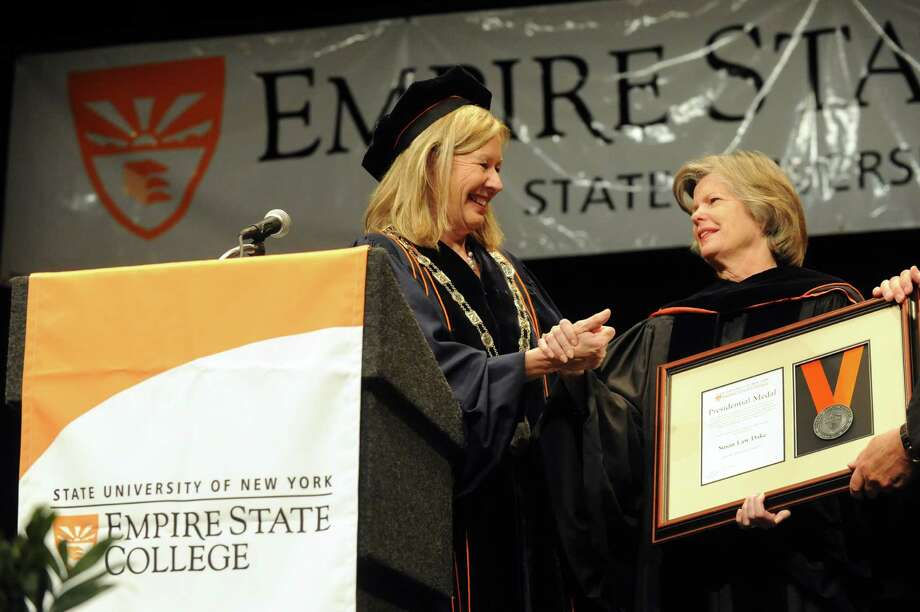 Empire State College acting president Meg Benke, left, gives Susan Dake, President of Stewart?s Foundation, the Presidential Medal Award during the Empire State College Northeast Center graduation commencement at the Egg on Saturday June 8, 2013 in Albany, N.Y. (Michael P. Farrell/Times Union) Photo: Michael P. Farrell