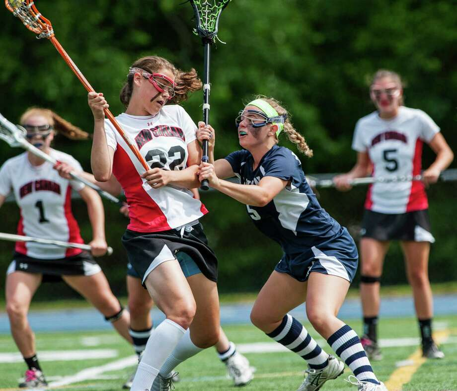 Wilton high school's Casey Tucker tries to keep New Canaan high school's Olivia Hompe from taking a shot during the CIAC division M girls lacrosse championship game played at Bunnell high school, Stratford, CT on Saturday June 8th, 2013. Photo: Mark Conrad / Stamford Advocate Freelance