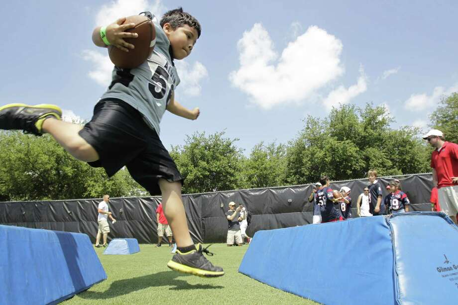 Nathan Contreras, 7, runs a drill during the Texans First Down Dads Field Day at Methodist Training Center in Reliant Park Saturday, June 8, 2013, in Houston. Photo: Melissa Phillip, Houston Chronicle / © 2013  Houston Chronicle