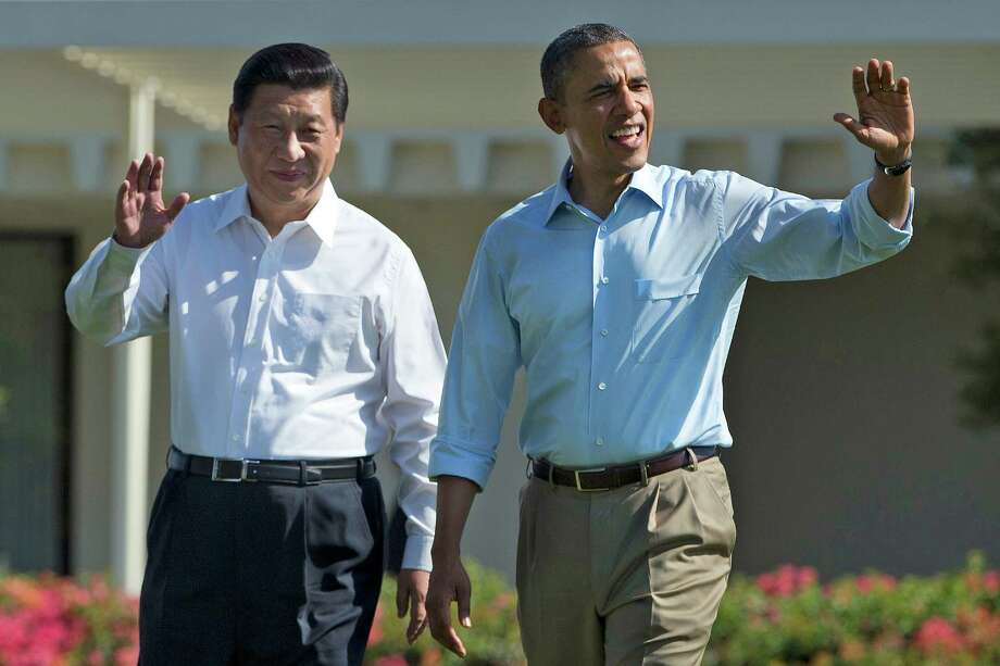 "President Barack Obama and Chinese President Xi Jinping, left, walk at the Annenberg Retreat of the Sunnylands estate Saturday, June 8, 2013, in Rancho Mirage, Calif. While saying it is critical that the U.S. and China reach a ""firm understanding"" on cyber issues, Obama told reporters his meetings with Xi have been ""terrific.""  (AP Photo/Evan Vucci) Photo: Evan Vucci, STF / AP"