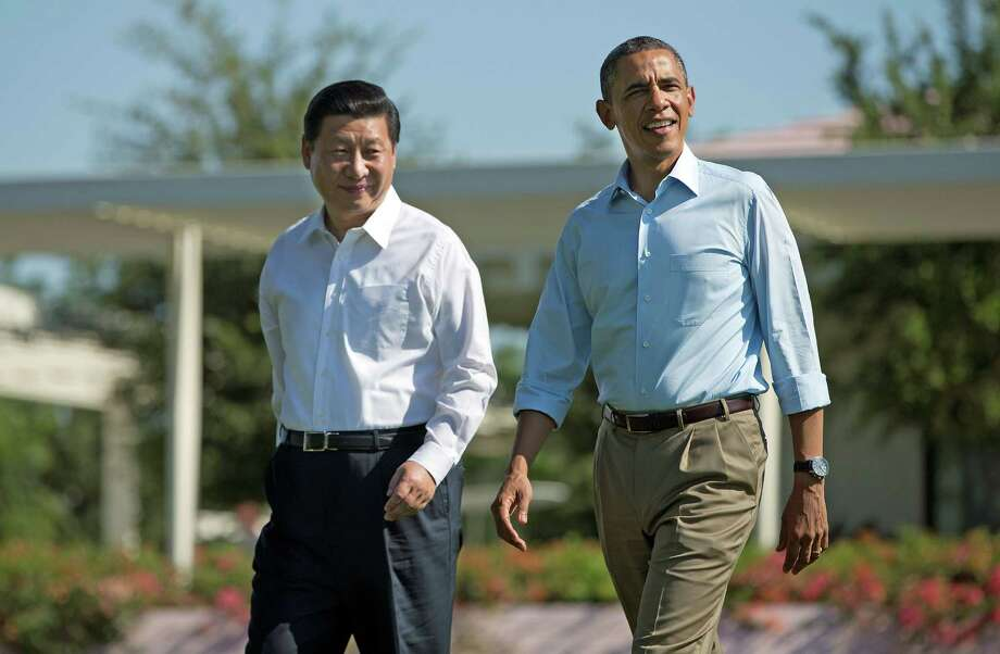 """President Barack Obama, right, walks with Chinese President Xi Jinping at the Annenberg Retreat of the Sunnylands estate Saturday, June 8, 2013, in Rancho Mirage, Calif. During their staged walk for the press Obama told reporters their meetings have been """"terrific."""" The issue of cyberespionage hangs over the summit, although both leaders carefully avoided accusing each other of the practice. (AP Photo/Evan Vucci) Photo: Evan Vucci, STF / AP"""