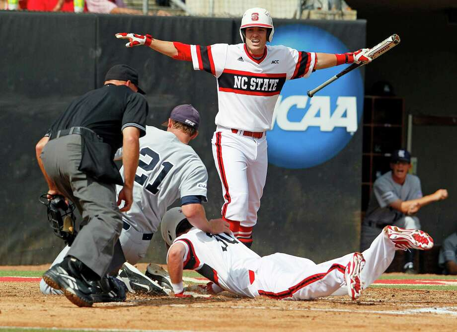 North Carolina State's Grant Clyde, top rear, signals safe as teammate Jake Fincher (30) scores after sliding into Rice's Austin Kubitza (21) on a wild pitch during the first inning of an NCAA college baseball tournament super regional game, Saturday, June 8, 2013 in Raleigh, N.C. (AP Photo/Karl B DeBlaker) Photo: Karl B DeBlaker, Associated Press / FR7226 AP