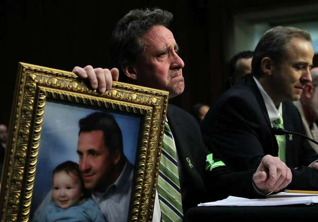 """WASHINGTON, DC - FEBRUARY 27:  Neil Heslin, father of six-year-old Sandy Hook Elementary School shooting victim Jesse Lewis, holds a picture of him with Jesse as he testifies during a hearing before the Senate Judiciary Committee February 27, 2013 on Capitol Hill in Washington, DC. The committee held a hearing on """"The Assault Weapons Ban of 2013.""""  EMS medical director of the Western Connecticut Health Network William Begg (R) also testified in the hearing.  (Photo by Alex Wong/Getty Images) Photo: Alex Wong, Getty Images / 2013 Getty Images"""