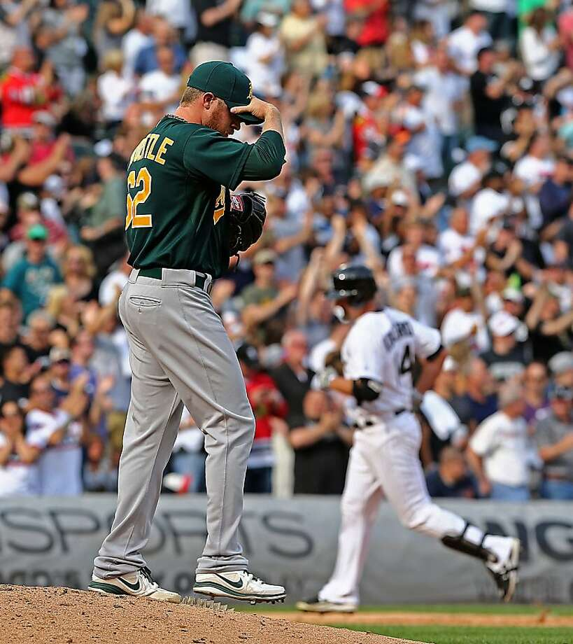Oakland Athletics pitcher Sean Doolittle, left, reacts as Chicago White Sox's Paul Konerko, right, rounds the bases after hitting a two-run home run in the eighth inning of a baseball game in Chicago, Saturday, June 8, 2013. (AP Photo/Charles Cherney) Photo: Charles Cherney, Associated Press