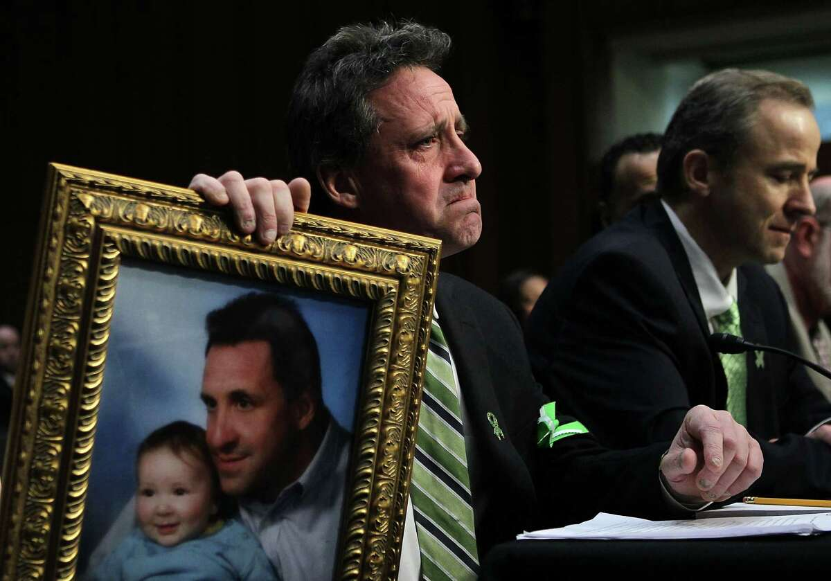 """WASHINGTON, DC - FEBRUARY 27: Neil Heslin, father of six-year-old Sandy Hook Elementary School shooting victim Jesse Lewis, holds a picture of him with Jesse as he testifies during a hearing before the Senate Judiciary Committee February 27, 2013 on Capitol Hill in Washington, DC. The committee held a hearing on """"The Assault Weapons Ban of 2013."""" EMS medical director of the Western Connecticut Health Network William Begg (R) also testified in the hearing. (Photo by Alex Wong/Getty Images)"""