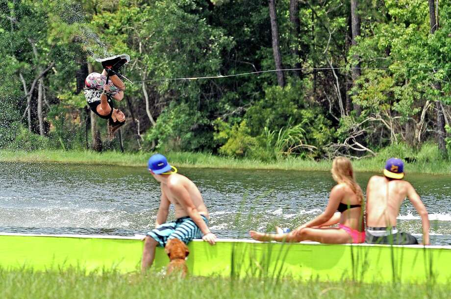 Spectators look on from a rail on the lake as Chris Leger competes in the SETx Mid Summer Classic wake boarding event in Rose City on Saturday, June 8, 2013. Photo taken: Randy Edwards/The Enterprise