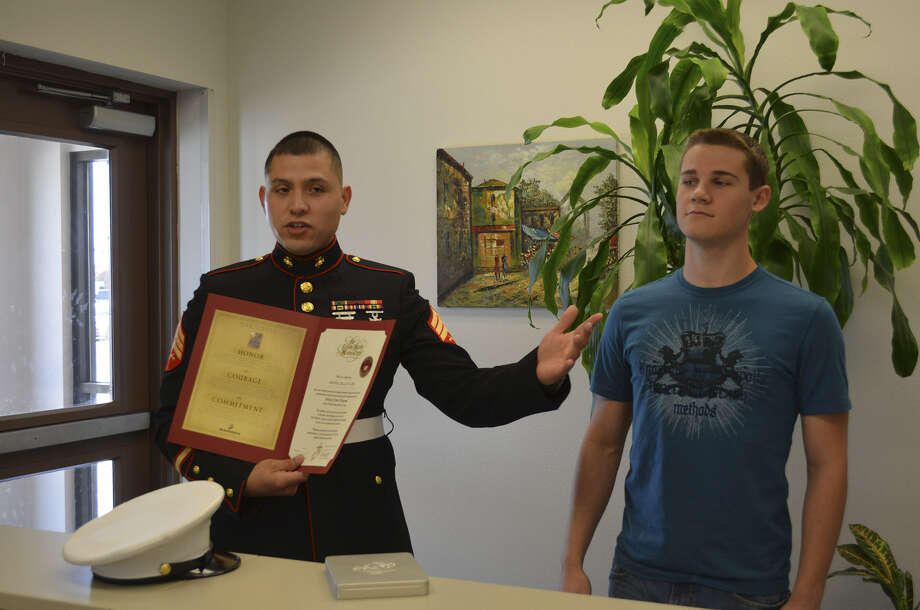 Dillon Adams, shown with Marine recruiter Sgt. Rogelio Estrada, finished in the top 10 percent of his senior class at East Central High School. For several years, he was homeless. Photo: Courtesy Photo