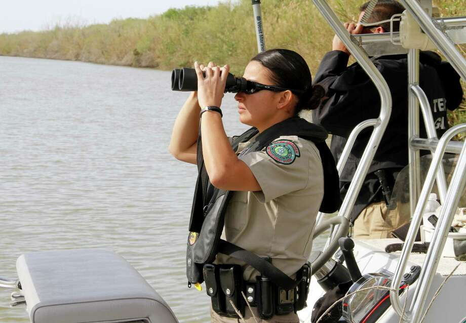 Texas game wardens Natali Mejia and Hector Leandro scan the Mexican side of the Rio Grande. Photo: Picasa
