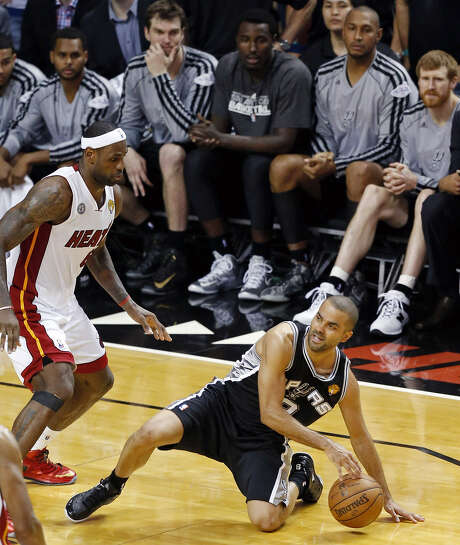 Tony Parker, maintaining his dribble, slips before going up and under LeBron James with a shot that sealed the Spurs' win in Game 1 of the NBA Finals. Photo: Edward A. Ornelas / San Antonio Express-News