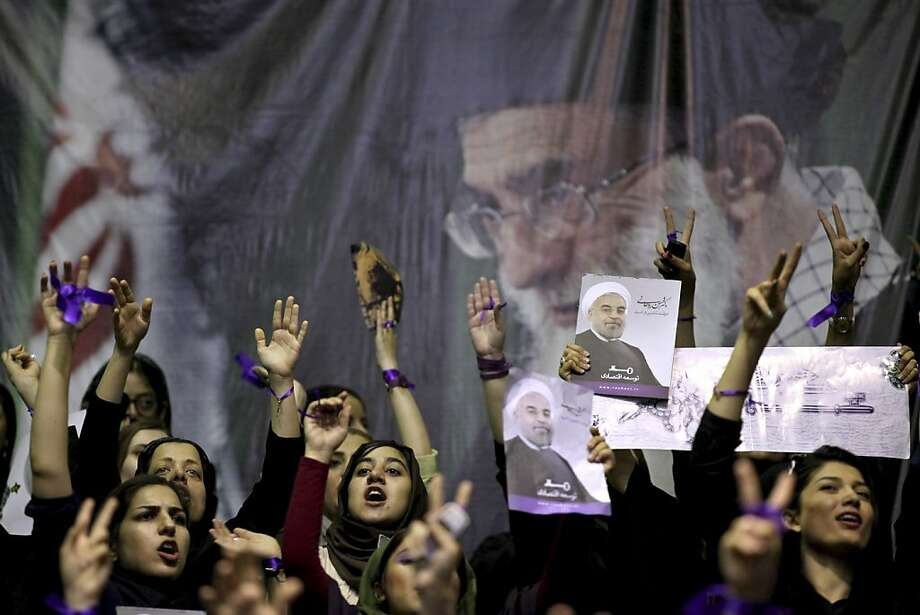 Female supporters of the Iranian presidential candidate, Hasan Rowhani, chant slogans, under a portrait of the Supreme Leader Ayatollah Ali Khamenei, during a campaign rally in Tehran, Iran, Saturday, June 8, 2013. Rowhani, a candidate in next week's presidential elections, says he will reset Iran's economy and will reverse President Mahmoud Ahmadinejad's foreign policy directions if elected. (AP Photo/Ebrahim Noroozi) Photo: Ebrahim Noroozi, Associated Press