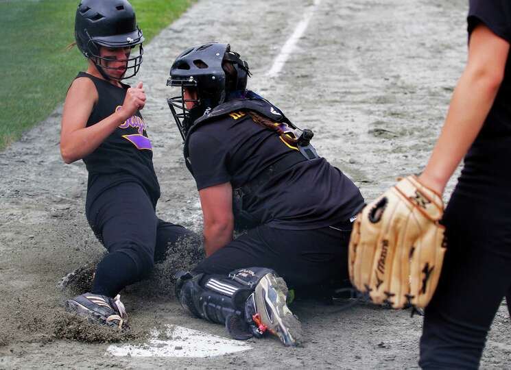 Troy High catcher Victoria Hallett, 3, attempts to block the plate from Maria Slager, 5, during the