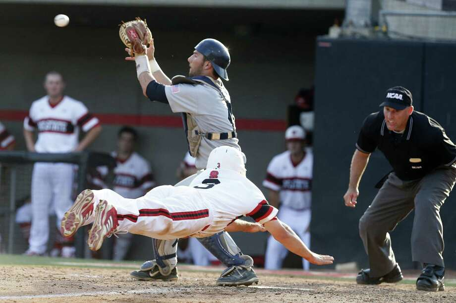 North Carolina State's Brett Williams dives for home to score the first of two runs in the bottom of the ninth as Rice catcher Hunter Kopycinski awaits the throw. Photo: Ethan Hyman, MBR / Raleigh News & Observer